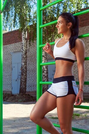 short shorts: Young sporty brunette woman in short shorts and  top posing next to sports horizontal bars on a summer day