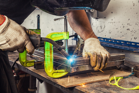 heavy construction: Close-up A strong man welder in a black T-shirt, welds a metal welding machine in the garage in the welding mask, blue sparks fly to the sides, protective glasses and tools are on the table