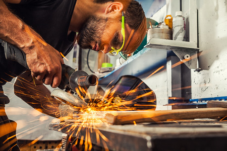 A young man welder a brunette in a black T-shirt and safety goggles. He processes a metal item from a angle grinder in the workshop. Close-up on the sides fly sparks from the  a angle grinder Stock Photo