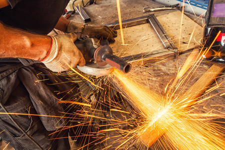 Close-up A young man welder grinds metal with an angle grinder  in the workshop, sideways flying sparks