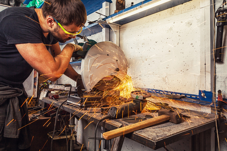 A young male welder cuts a metal with a circular saw in the garage, a lot of tools are on the table