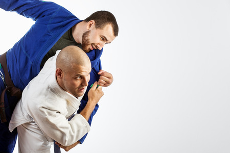 Two young men in a blue and white kimono fight judo , Jiu Jitsu on an isolated white background