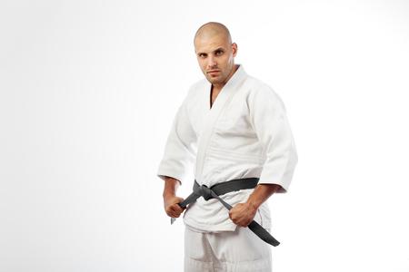 Young sports man in white kimono for sambo, judo, jujitsu posing on white background, looking straight, standing sideways Stock Photo