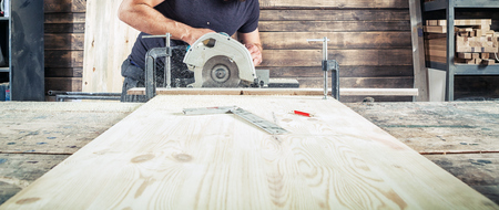 A young brunette man in a black T-shirt is sawing a tree with a modern circular saw in the workshop Stock Photo
