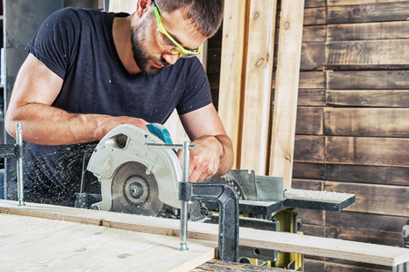 furniture design: A young brunette man in a black T-shirt is sawing a tree with a modern circular saw in the workshop Stock Photo