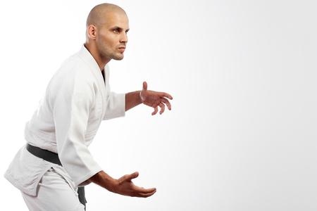 Young sporty man in white kimono for sambo, judo, jujitsu posing on white background, standing position