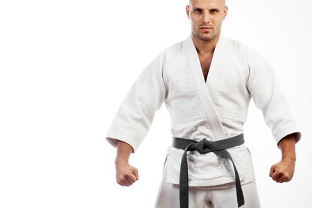Young athletic man in white kimono for sambo, judo, jujitsu posing, looking straight, position of fighting post, hands clasped in fist