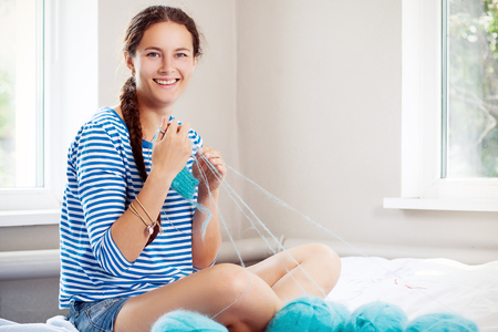 A young woman with a single pigtail in a striped blouse and short shorts sits, smiles and knits with knitting needles and blue natural woolen threads a sweater on the background of two large windows Stock Photo