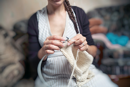 A young woman knits in a striped dress knits with white woolen knitting wool a warm winter sweater and sits at home on the couch Stock Photo