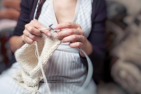 Een jonge vrouw breist in een gestreepte jurkbreien met witte wollen breienwol een warme wintertrui en zit thuis op de bank