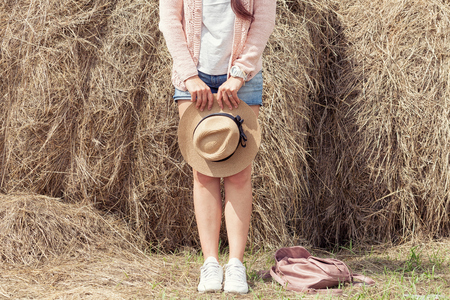 A young woman in denim shorts and a pink knitted cardigan is holding a straw hat in the hands of a haystack in a summer day