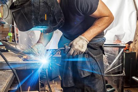 Een mannenlasser in een zwart T-shirt, bouwhandschoenen en een lasmasker werkt enthousiast en wordt in de werkplaats met een lasmachinemetaal gelast