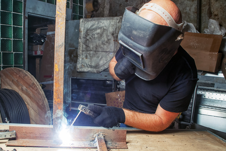 light duty: A bald, strong man in a black welding mask is brewing a metal welding machine in a dark old garage, working with a welding machine, around a lot of tools for work