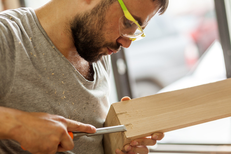 A dark-haired man with a beard and protective green glasses treating a wooden product with a chisel in the workshop, close-up, side view