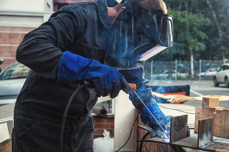A strong man welder in a construction black overall and welding brush welds a welding machine with a mettalic design on the street, in the background a city park and green trees