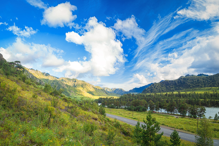Landscape of the Altai mountains on a summer day. An automobile road that goes to the distance into the mountains between the green coniferous forest, the blue sky with clouds in the mountains