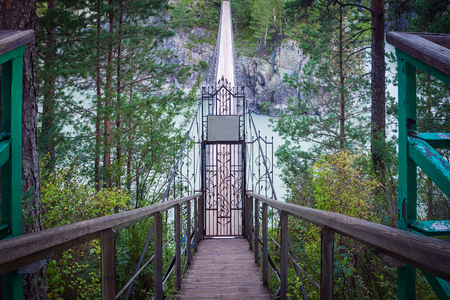 katun: Narrow suspended bridge of metal structures and wood with a gate for entry over a mountain river. The bridge over the mountain river going to the distance in the mountain Altai to the island of Patmos
