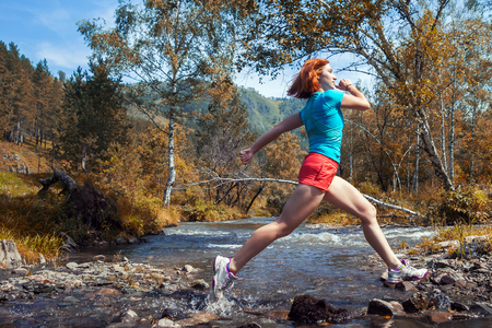 staying fit: A young red-haired woman in a blue T-shirt and sporting shorts runs down a mountain river, jumps over rocks in a mountainous area of Altai and a green coniferous and deciduous forest on an autumn day