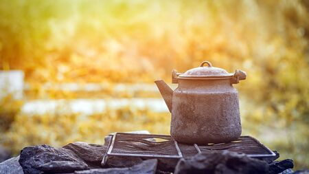 An old cast-iron burnt kettle stands on a black rimmed grate on the rocks and warms the water on the nature in the mountains on a summer day. Still life of things on a mountain theme Stock Photo