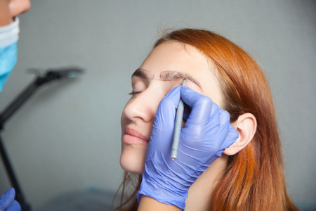 threading hair: The master on the eyebrows draws the shape of the grafted eyebrow shape in a blue medical disposable gloves red-haired beautiful woman on a gray background Stock Photo