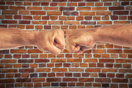Two mens strong hands clenched into fists are connected together on a brick background. Sign of male power in fists, male greeting Stock Photo