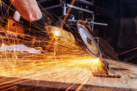 Close-up of a man sawing metal with a hand circular saw on a wooden table in the workshop, in the background a lot of generalization, yellow sparks fly away in different directions