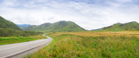 The landscape of the Altai mountains, the Chemal region, covered with green forest, grass and road leaving in the distance on a summer day, the sky is blue with cirrus clouds