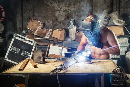 Un giovane saldatore maschio in una maschera di saldatura senza una maglietta dimostra la sua forte pressione e muscoli della mano e saldature in metallo con saldatrice su un tavolo di legno in officina, scintille blu da saldatura Archivio Fotografico