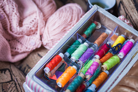 unbound: The still life of a tangle of pink woolen threads, an unbound pink sweater and a multitude of coils of thread of different colors in the box in even rows lie on a brown vein, the top view