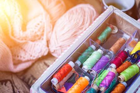 The still life of a tangle of pink woolen threads, an unbound pink sweater and a multitude of coils of thread of different colors in the box in even rows lie on a brown vein, the top view