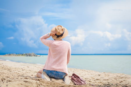 young woman in a pink cardigan, straw hat and jeans shorts sitting on the sand and looking at the sea on a summer clear day. Relax near the sea, summer delight