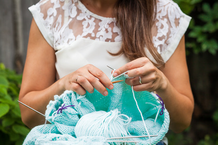 Close-up of a young dark-haired woman in a white silk top knits with natural woolen threads a mint fashionable sweater Stock Photo