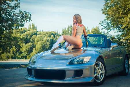 Young sporty sexy blond woman with small afro-pigtails in a gray swimsuit, white golfs, white sneakers sitting on the hood of a gray car on a summer day, in the background of green trees Stock Photo