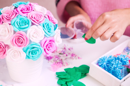 spongy: Close-up of a woman with red nails makes a bouquet of artificial flowers of roses from foam in a white pot on a white isolated background. Roses blue, pink, white for decoration of weddings, interiors Stock Photo