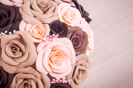 Close-up of artificial flowers of roses from fameirana, made in hand, collected in a bouquet in a white pot on a table of beige color. Roses of the coarse, beige and peach color