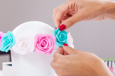 Close-up woman with red nails collects a bouquet from artificial flowers of roses from foam in a white pot on a white isolated background. Roses blue, pink, white for decoration of weddings, interiors