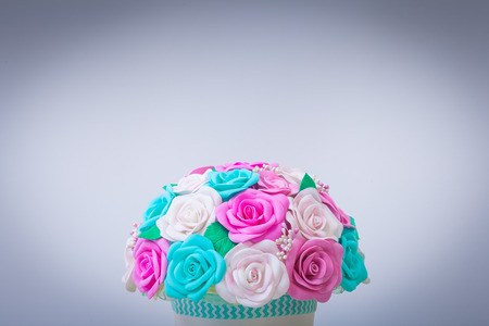 spongy: close-up of artificial flowers of roses from foam in different colors of blue, pink, white in a white pot made with their own hands for decorating weddings, interiors and holidays on a swivel table