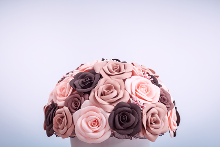 Close-up of artificial flowers of roses from foam, made in hand, collected in a bouquet in a white pot on a table of beige color. Roses of the coarse, beige and peach color Stock Photo