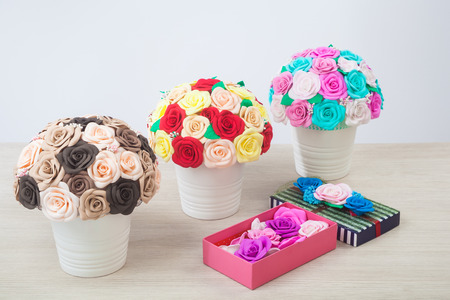 Artificial flowers of roses from foam in different colors  in white pots and a few wooden boxes decorated with roses, made with their own hands for decorating weddings, interiors and holidays Stock Photo