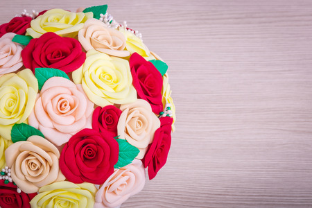 Artificial flowers of roses from Fahmiran red, beige, yellow, collected in a bouquet in a white pot stand on a light wooden table for decoration of interiors and weddings, top view Stock Photo