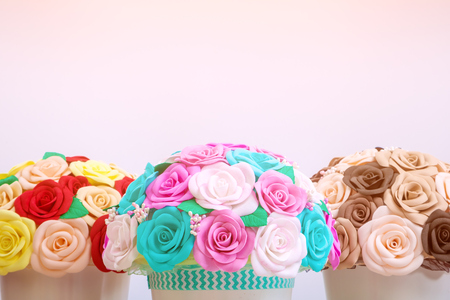 spongy: Artificial flowers roses from foam pink, blue and white, red, yellow, brown, collected in a bouquet in three white pots stand on a light wooden table for decorating interiors and weddings