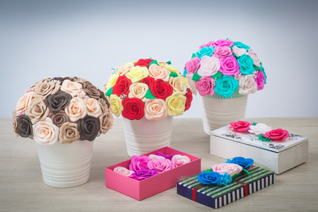 Artificial flowers of roses from foam pink, blue and white, red, yellow, brown, collected in a bouquet in three white pots and boxes decorated with roses stand on a light wooden table