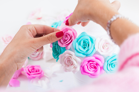 Close-up Young woman making her own hands artificial flowers roses from foam blue, pink white on a light table for decorating weddings and gifts
