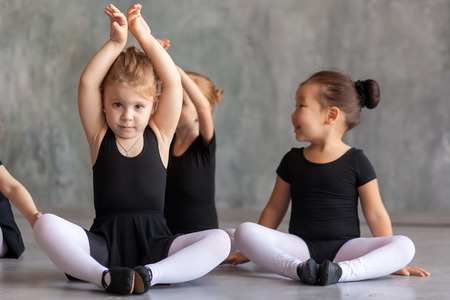 A blonde girl and a small Asian girl in black swimsuits, white tights and pointe shoes sit on the pound and stretch before a ballet in a dark dance studio Stock fotó