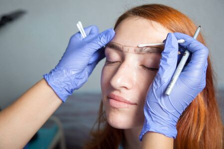 threading hair: A close-up of the beautician, the stylist dzadeb eyebrow correction and draws the correct shape of the eyebrows in blue medical gloves red-haired woman