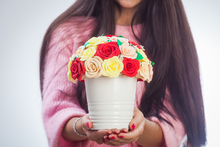 A close-up of a young dark-haired woman in a pink knitted sweater is holding a white pot of artificial flowers with roses from the foam of a dull, red and beige color Stock Photo