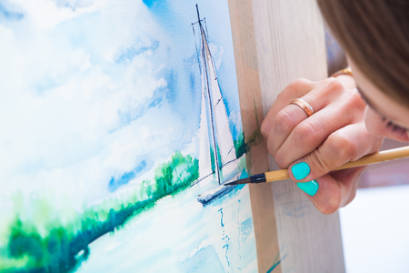 Young dark-haired woman painter watercolor painting and wooden brush on white paper seascape with a single-deck yacht