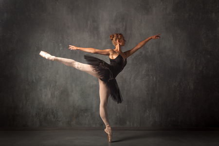 Beautiful attractive blonde woman primer ballerina in a black dance pack, white pantyhose and pointe shoes beautifully dances ballet in a dark studio