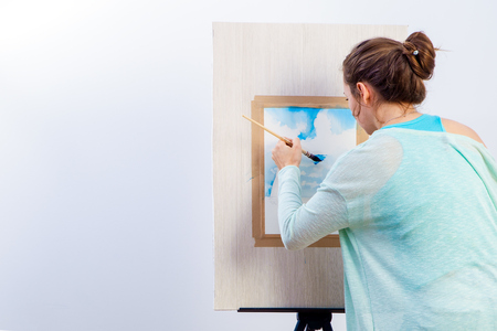 Young dark-haired woman artist in blue sweater paints with watercolor and wooden brush on white paper seascape with single-deck yacht Stock Photo