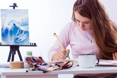 young dark-haired female artist paints a picture of a watercolor behind a white table, in the background a picture of the sea in a light studio Stock Photo